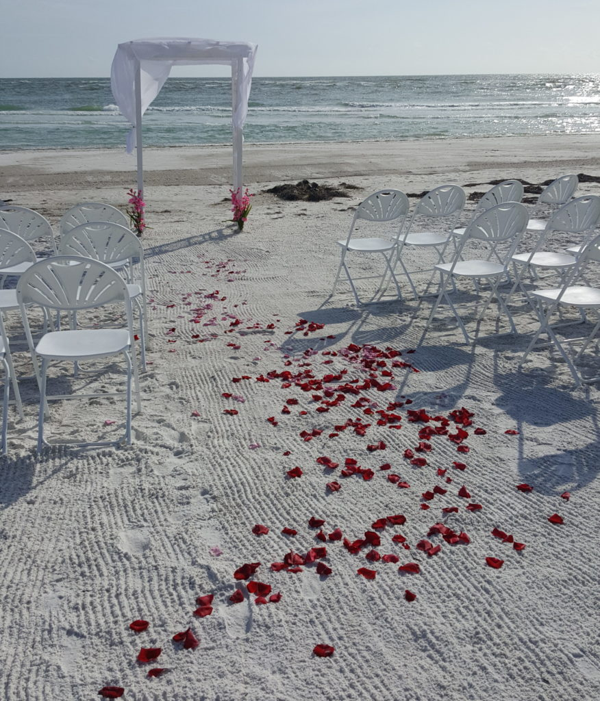 White arbor with chairs and rose petal aisle runner