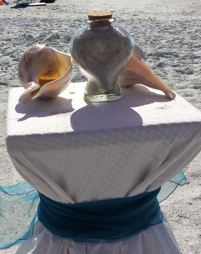 Sand ceremony uses beach sand and shells to pour sand into the center container.