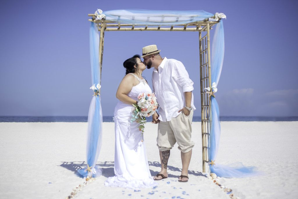 Jocelyn and Title under the bamboo arbor with starfish and turquoise fabric that I put together for their Clearwater Beach wedding ceremony. Picture by C.R. Newman Photography.