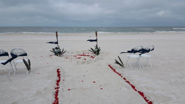 Clearwater special #2 with A la Carte mound rose petal heart in the sand with tiki torches, greenery, and hydrangea's.